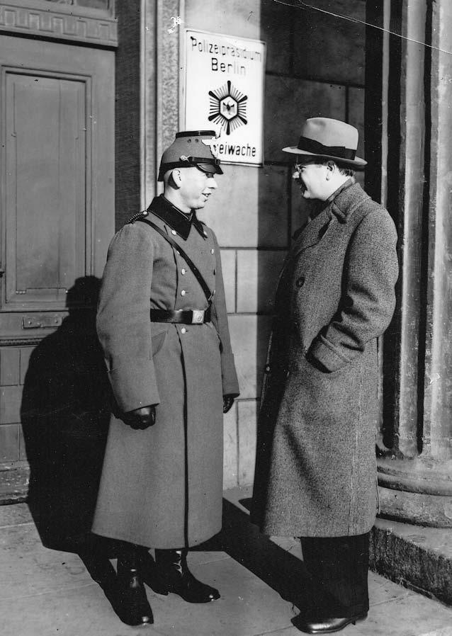 Talking to a German policeman, Berlin, circa 1940.